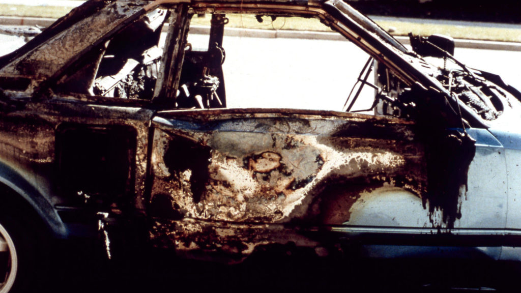 The remains of Mark Hofmann's vehicle after the third bombing, Murder Among the Mormons, episode 1. c. Courtesy of Netflix © 2021