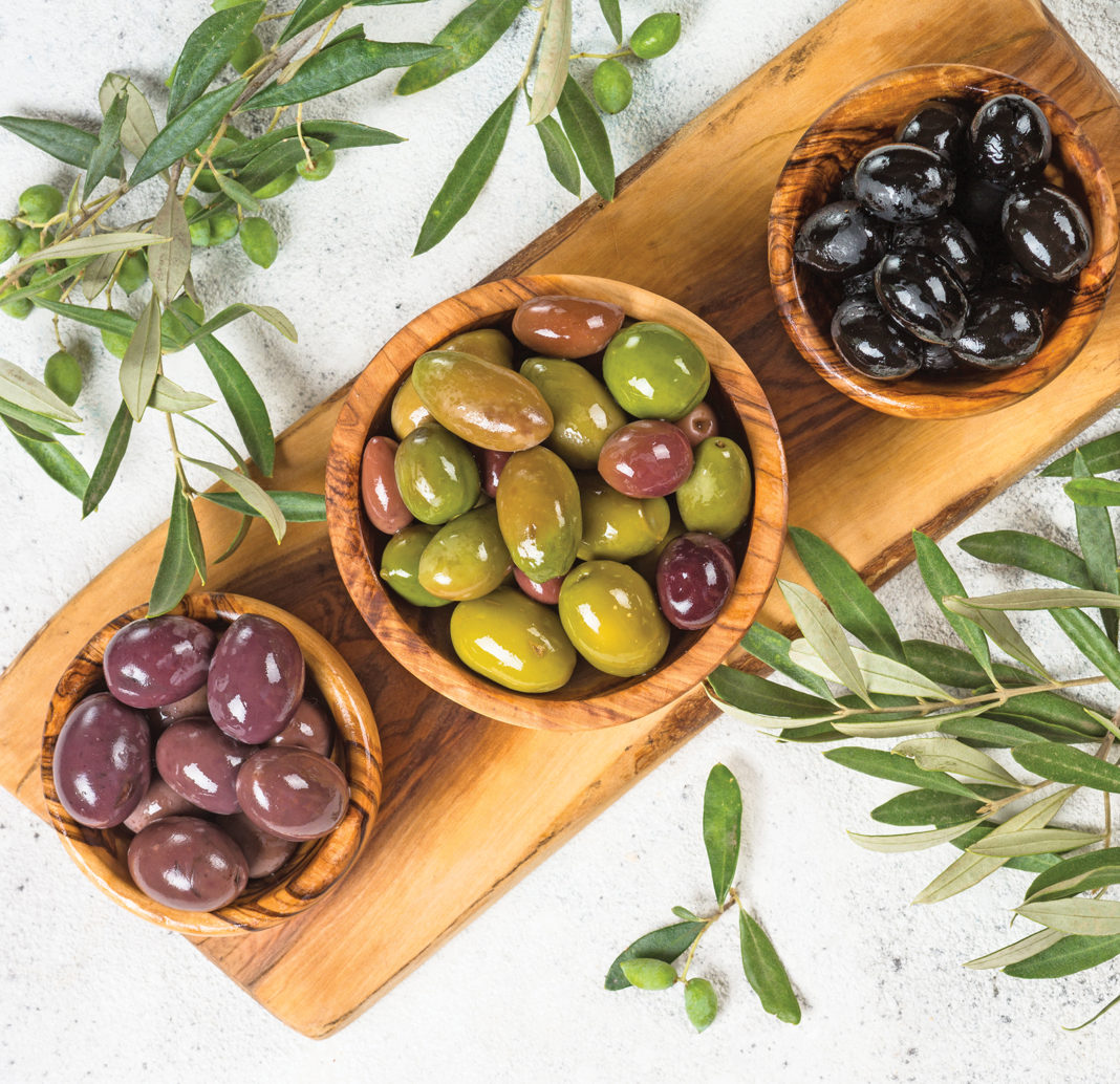 Black and green Olives in wooden bowls on white stone background.