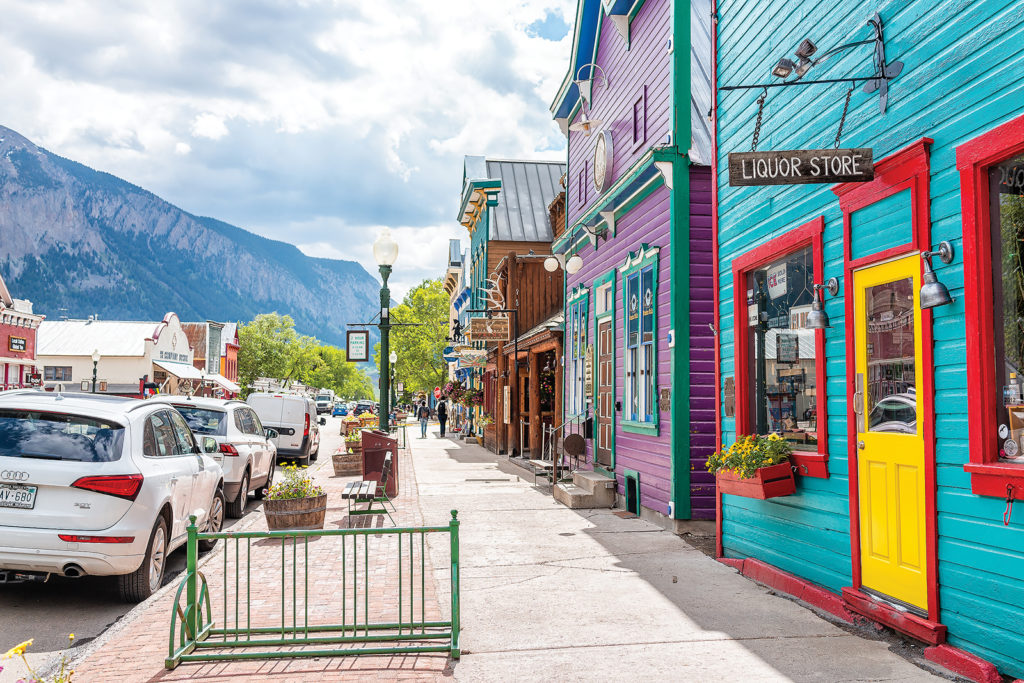 Crested Butte, USA - June 21, 2019: Colorado colorful vivid village houses stores shopping downtown in summer with vintage mountain architecture and cars on street