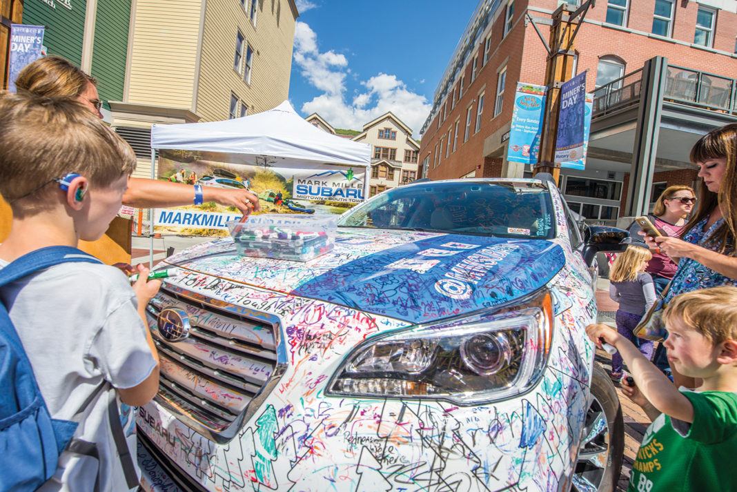 Children gather around a decorated car at Park Silly, a summer market in Park City,