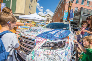 Children draw on a Subaru during Park Silly Sunday Market