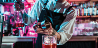 Expert barman is making cocktail at night club or bar. Glass of fiery cocktail on the bar counter against the background of bartenders hands with fire. Barman day concept