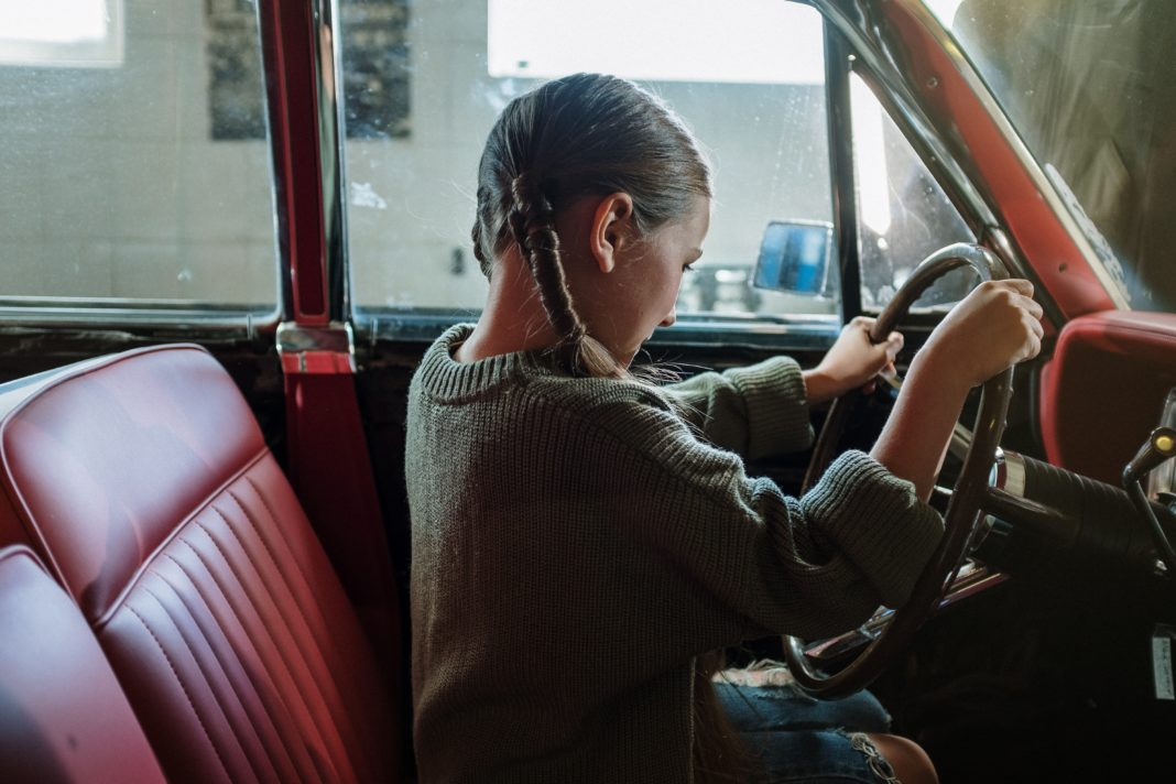 photo of young girl behind the wheel of a vehicle