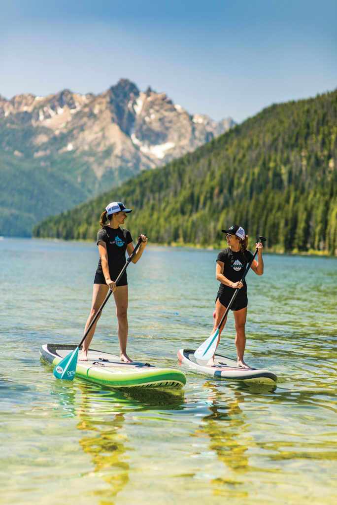 Stand up paddle boarding at Redfish Lake with Sawtooth Mountains in background near Stanley, Idaho